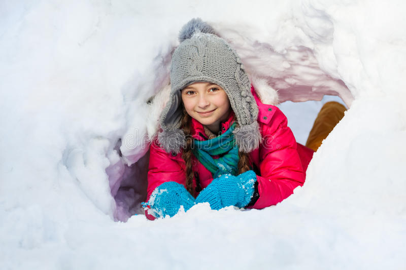 Girl is playing outside in tunnel she dug of snow. A cute young girl is playing outside in tunnel she dug of snow on a winter day royalty free stock photo