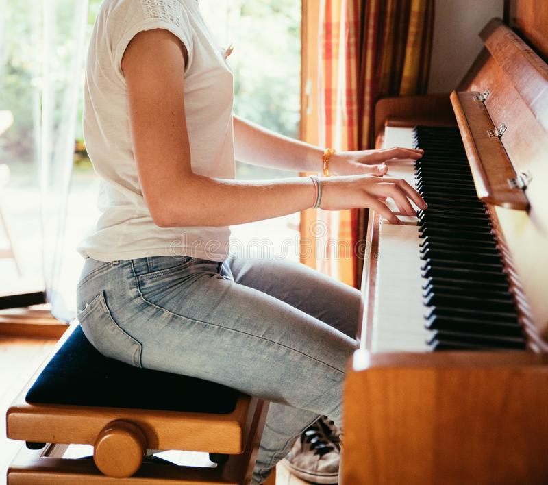 Girl is playing piano at home, high angle view, blurry background stock photography