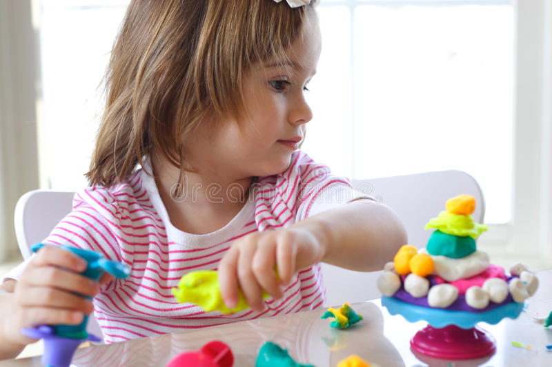 Girl playing with play dough stock photography