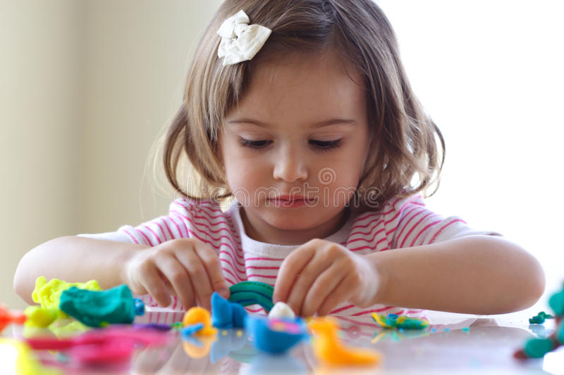 Girl playing with play dough stock image