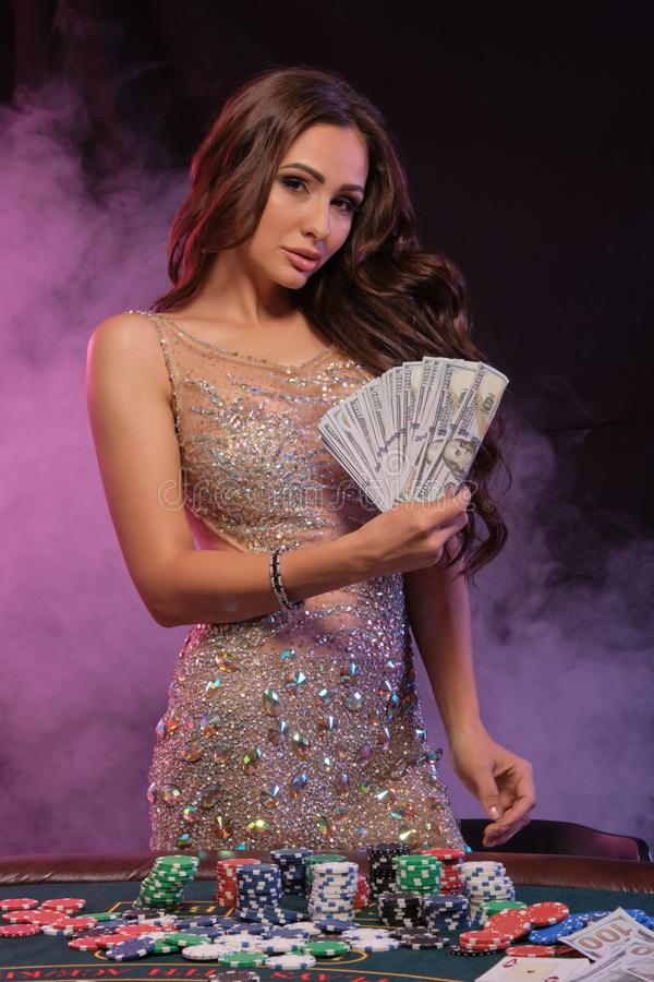 Girl playing poker, casino. Holding cash, posing at table with stacks of chips, money, cards. Black, smoke background royalty free stock images