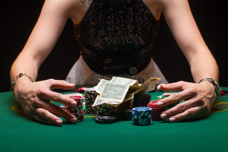 Girl playing poker and picks up her winnings with money and chips. Horizontal shot in a night game club. Casino Concept, Player, royalty free stock photos