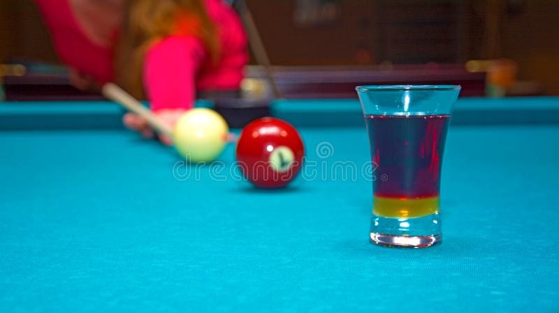 Girl playing pool, has the ball and is reflected in the glass stock images