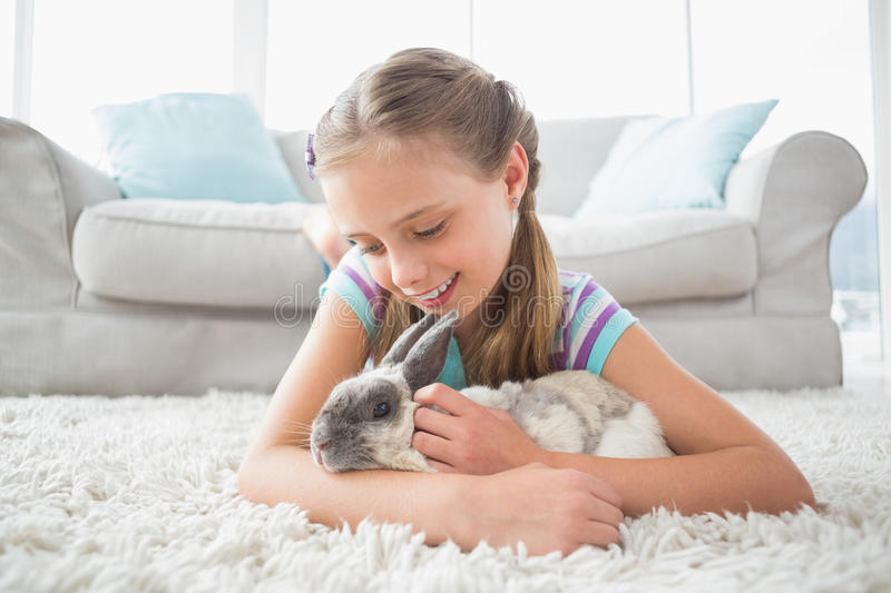 Girl playing with rabbit in living room stock images