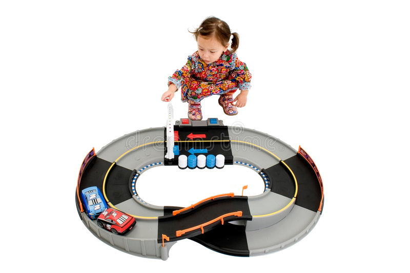 Girl playing with racetrack. Young girl playing with cars on a racetrack stock image