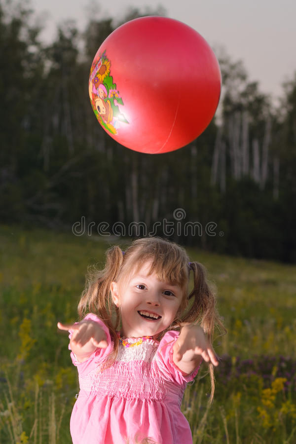 Girl playing with a red ball in the park stock photos