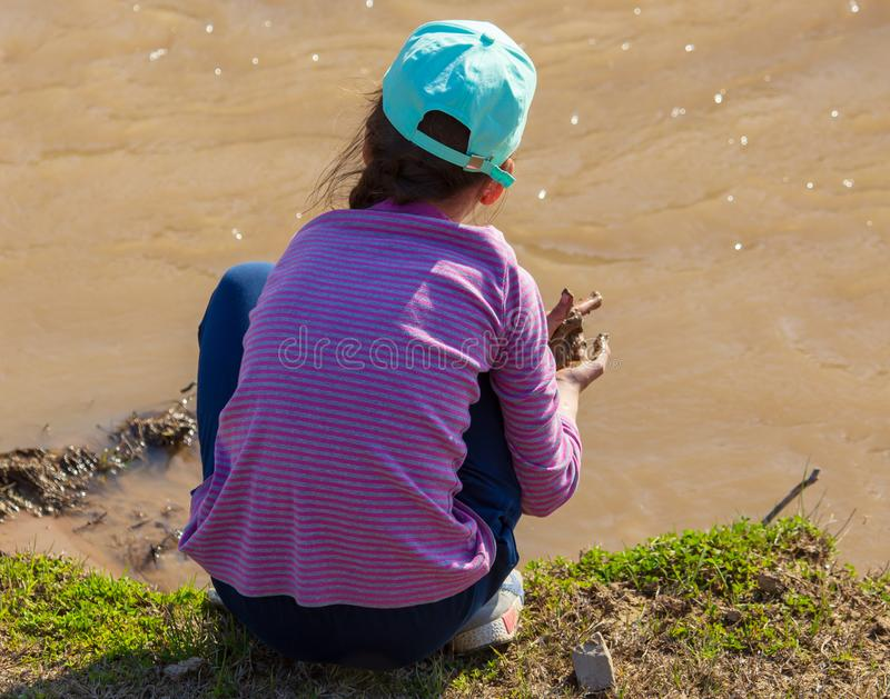 Girl playing on the river bank in nature stock photo