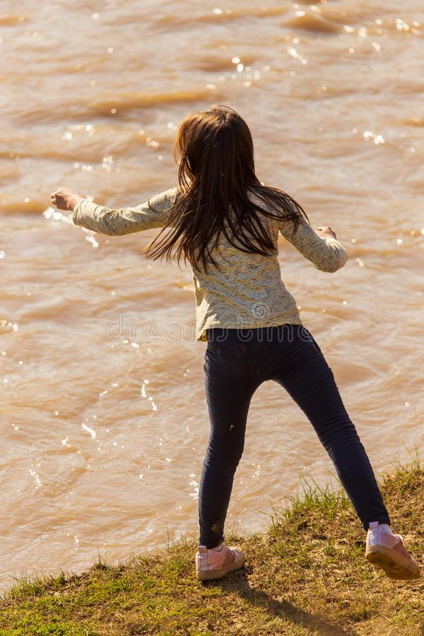 Girl playing on the river bank in nature royalty free stock photos