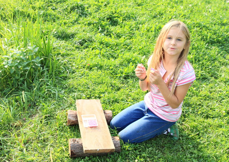 Girl playing with rubber bands stock photo