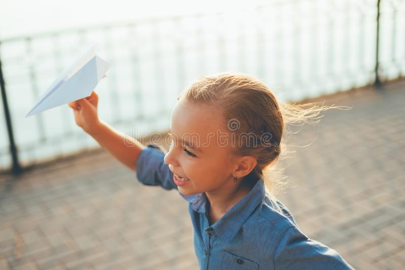 Girl playing, running with toy paper airplane. Close-up of girl playing, running with toy paper airplane in the park, on gray pavage near lake in denim dress stock image