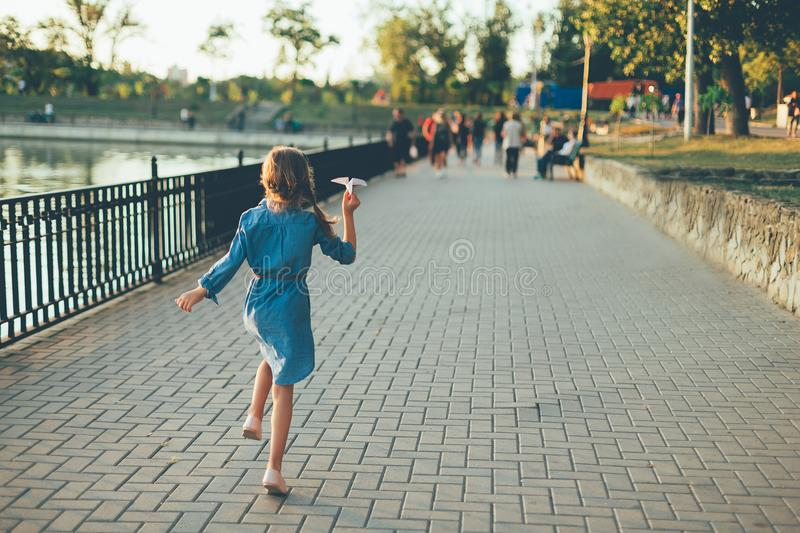 Girl playing, running with toy paper airplane. Outdoor back view of child playing, running with toy paper airplane in the park, on gray pavage near lake in denim royalty free stock photos
