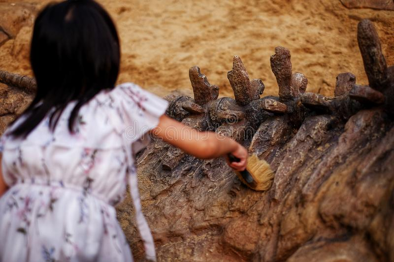 A girl playing in a sandbox with a modeled dinosaur fossil, brushing sand off the fossil royalty free stock photo