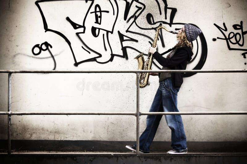 Girl playing saxophone royalty free stock photo