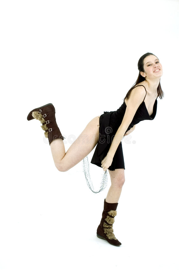 Girl playing with shawl. Young dancer, in black short skirt and trendy fur boots, jumping on a white studio background royalty free stock images