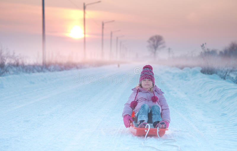 Girl playing with sleigh in the snow. On street royalty free stock images