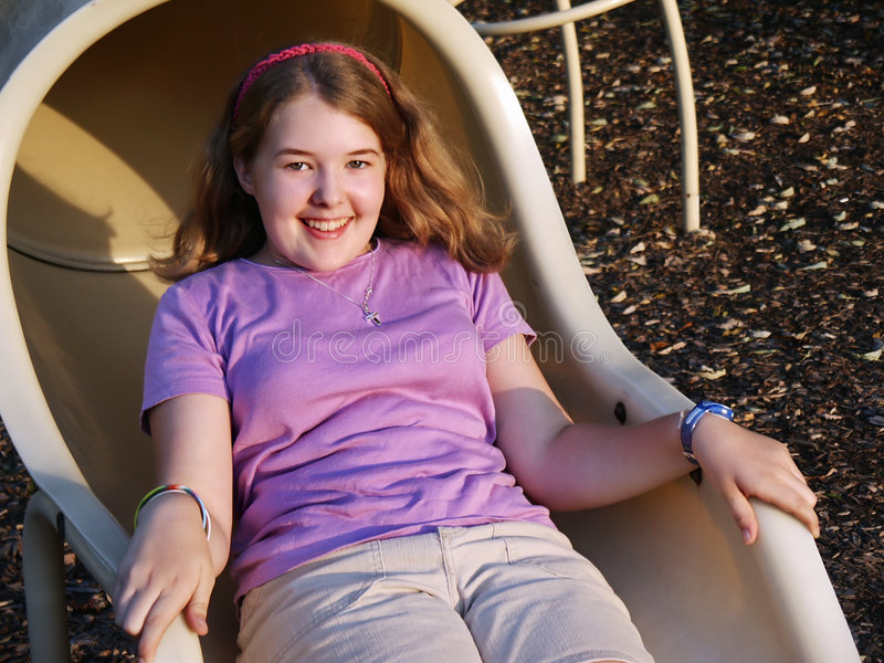 Girl playing on slide royalty free stock images