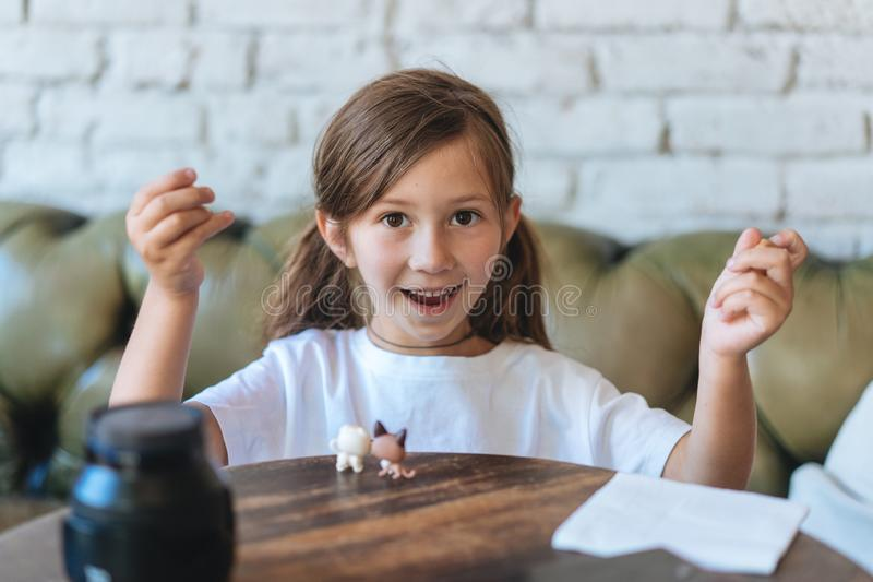 Girl playing with small figures sitting on soft stock photography