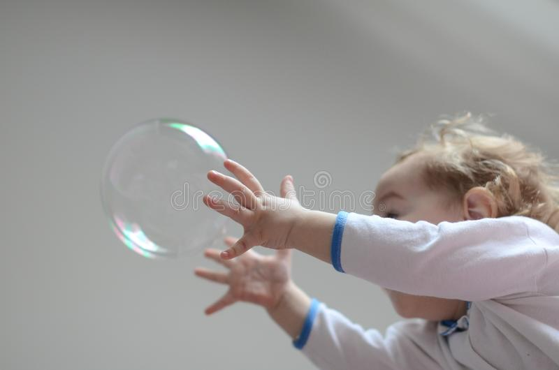 Girl playing with soap bubbles stock photos