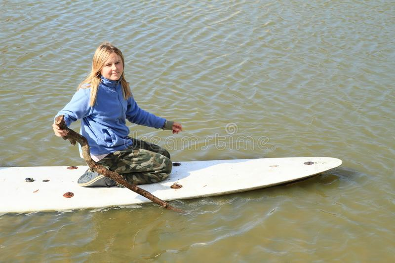 Girl playing on surf. Young girl - kid playing with wooden stick on surf board in water of pond stock image