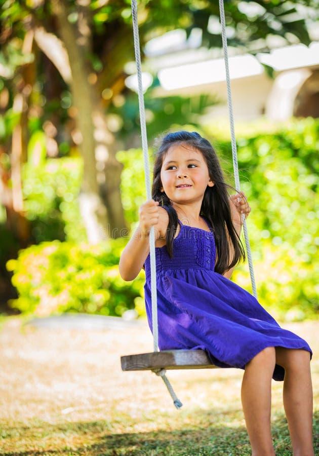 Girl Playing on Swing Set royalty free stock image