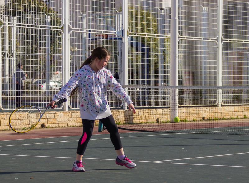 Girl playing tennis on the court stock image