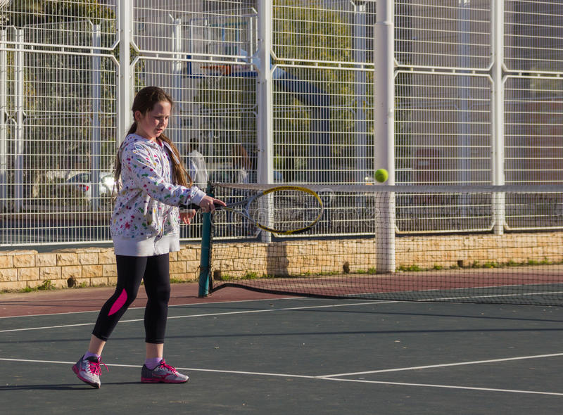 Girl playing tennis on the court royalty free stock image