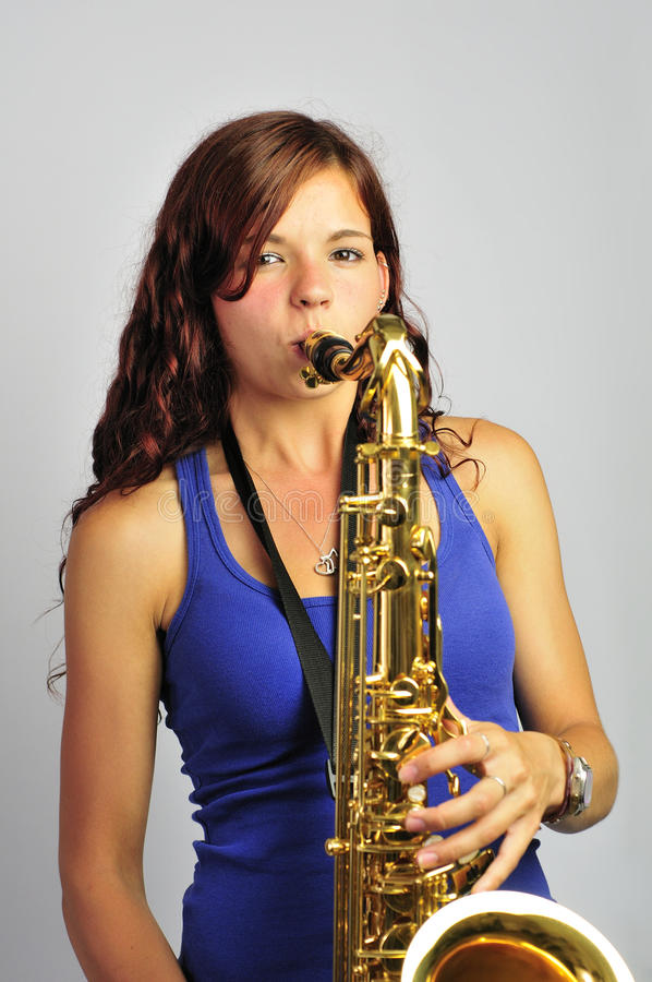 Girl Playing Tenor Saxophone. Pretty girl smiles towards the camera whilst playing tenor sax stock photos