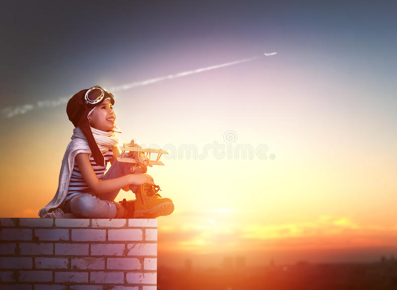 Girl playing with toy airplane. A child plays with a toy airplane in the sunset and dreams of becoming a pilot stock image