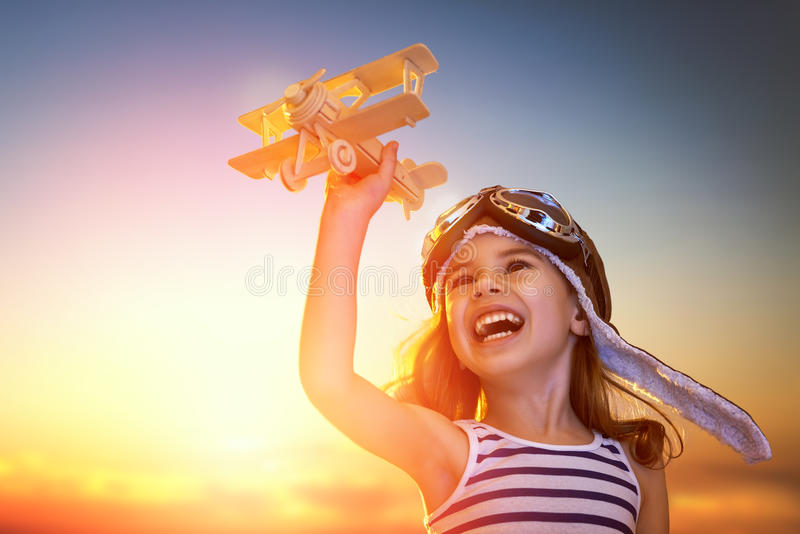 Girl playing with toy airplane. Dreams of flight! child playing with toy airplane against the sky at sunset stock photography