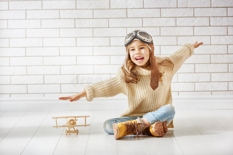 Girl playing with toy airplane. Happy child girl playing with toy airplane. the dream of becoming a pilot royalty free stock images
