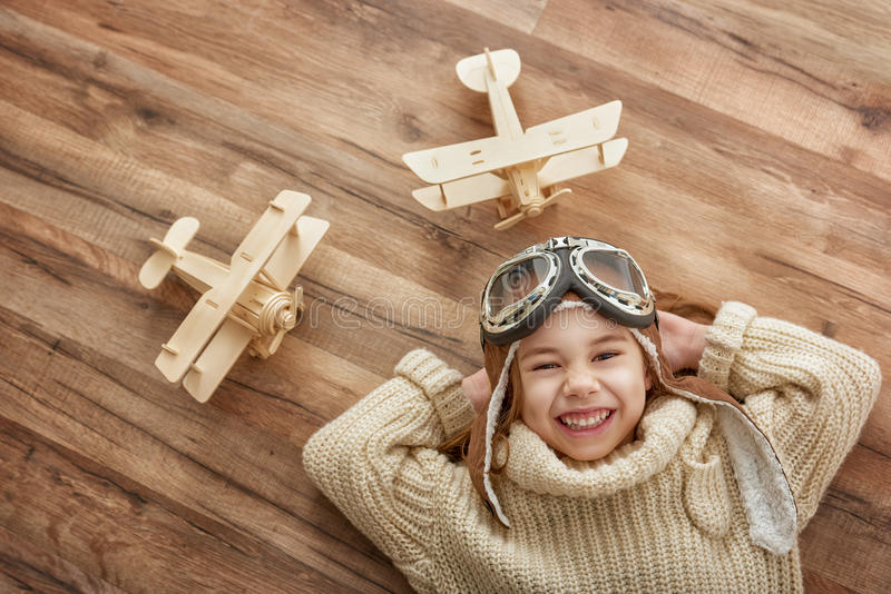 Girl playing with toy airplane. Happy child girl playing with toy airplane. the dream of becoming a pilot stock photo