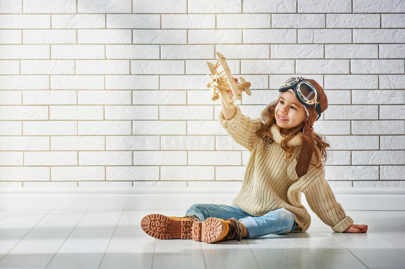 Girl playing with toy airplane. Happy child girl playing with toy airplane. the dream of becoming a pilot stock image