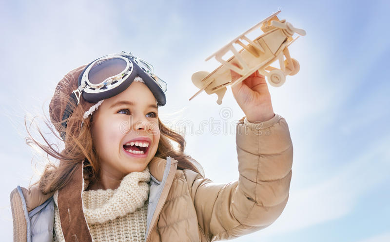 Girl playing with toy airplane. Happy child girl playing with toy airplane. the dream of becoming a pilot royalty free stock image