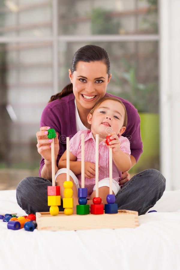 Girl playing toy with mother