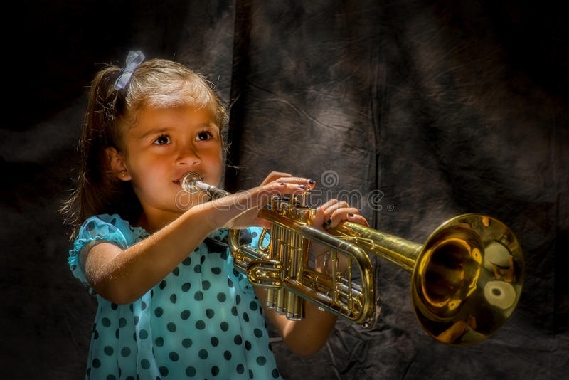 Girl playing a trumpet royalty free stock photos