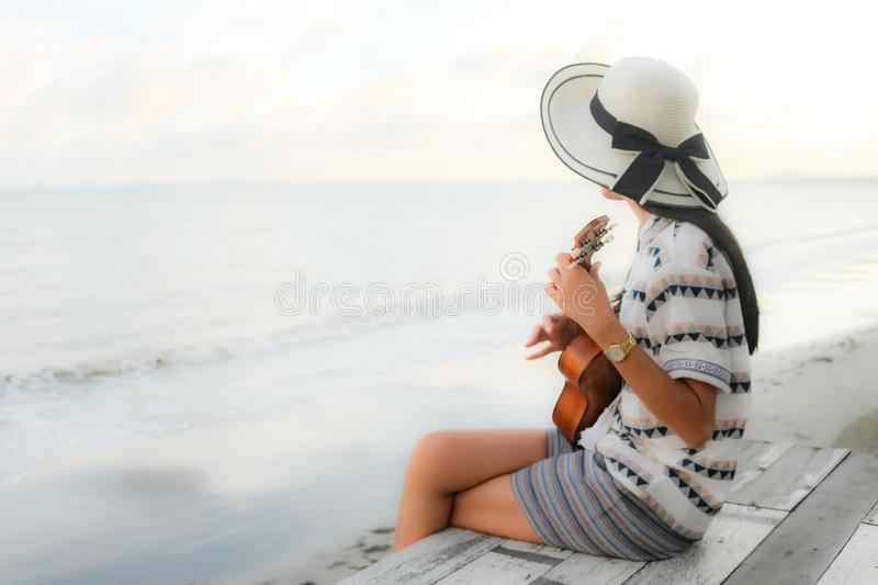Girl playing ukulele in the beach royalty free stock images