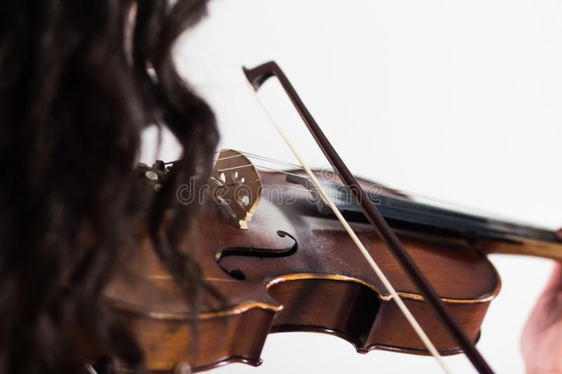Girl playing the violin. Close-up. View from the shoulder side through the hair. The bow touches the strings. Musical theme. White stock images