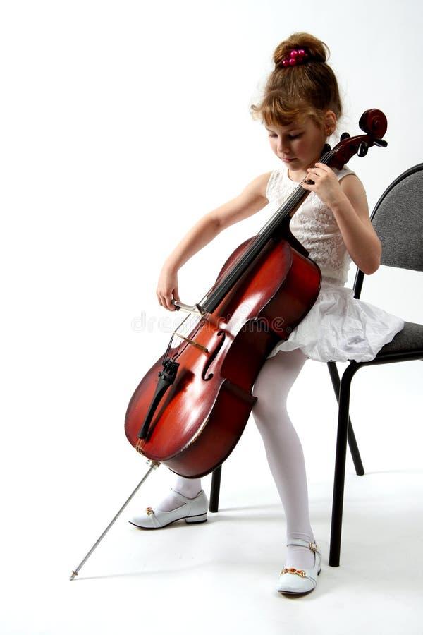 Girl playing on violoncello stock image