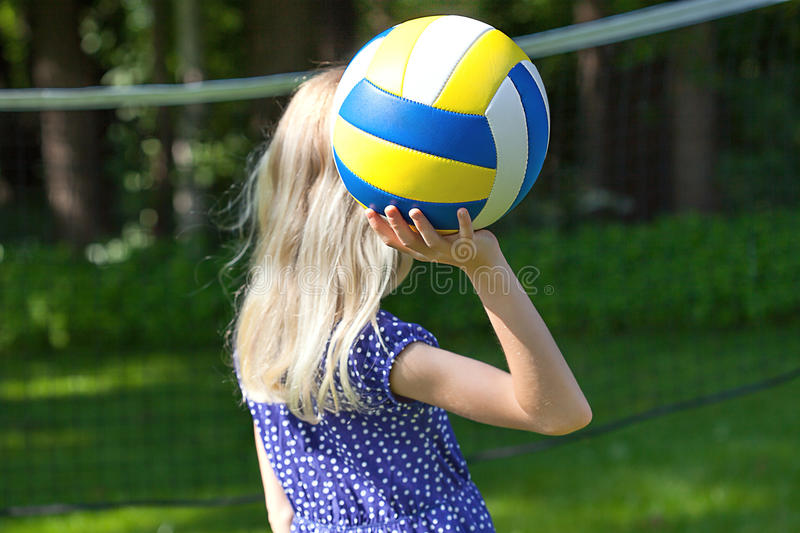 Girl playing volleyball. A blonde girl playing volleyball oudoors royalty free stock photos