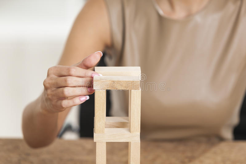 Girl is playing with wood bricks. Woman in beige is playing with wooden bricks at her workplace in a white office. Concept of a break stock photography