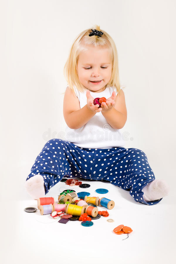 Girl are playing with yarn and buttons royalty free stock image