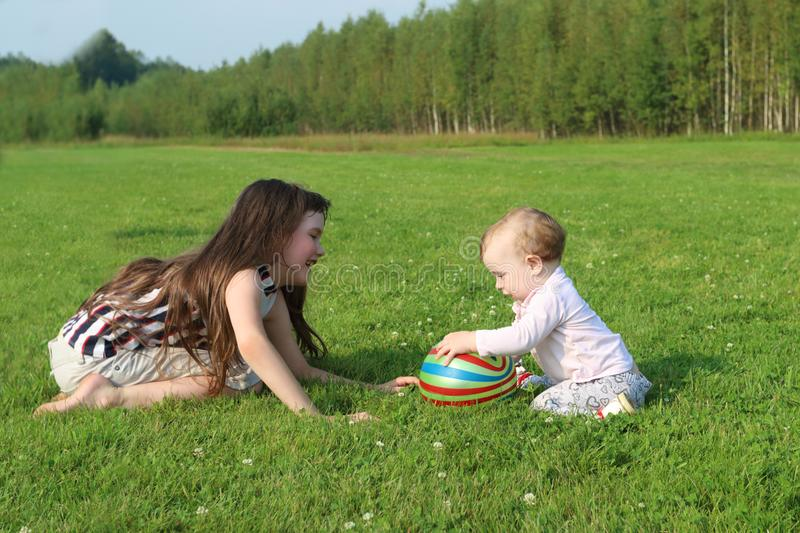 Girl plays with baby and ball on green field at summer stock photography
