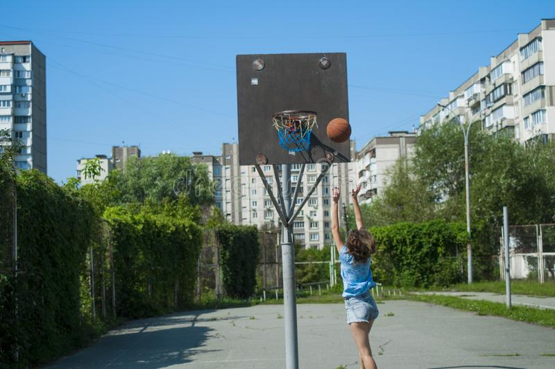 The girl plays basketball on the street. stock photos