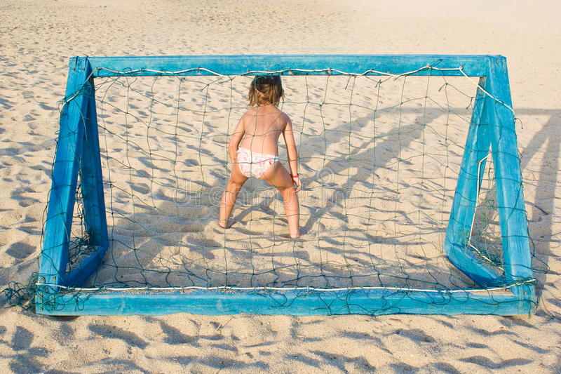 Girl plays beach soccer stock image