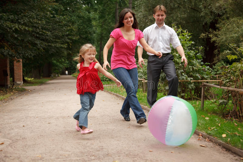 Download Girl Plays With Big Ball In Park With Parents Stock Image - Image of cheerful, parent: 13021113