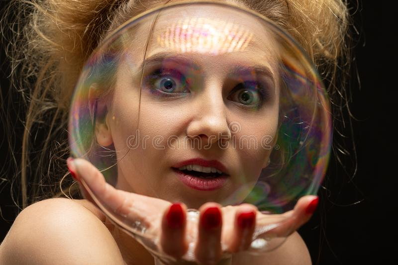 Girl with soap bubbles. Girl plays with big soap bubbles on black background royalty free stock photography