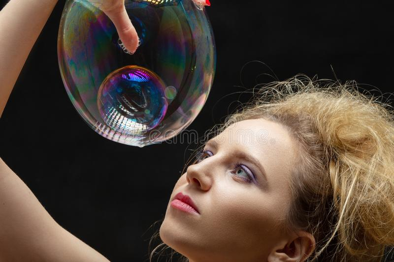 Girl with soap bubbles. Girl plays with big soap bubbles on black background royalty free stock images