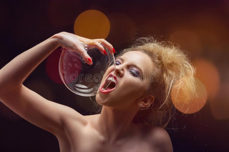 Girl with soap bubbles. Girl plays with big soap bubbles on black background with lights stock photo