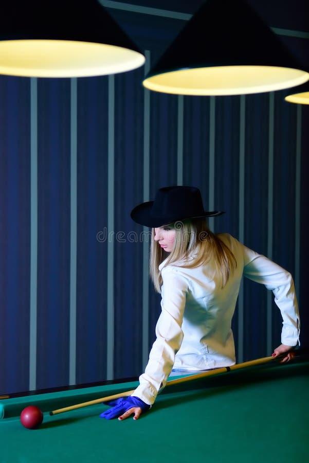 The girl plays billiards stock photos