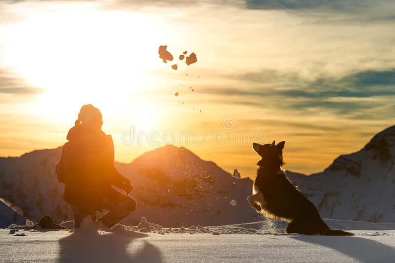 Girl plays with border collie. In the snow